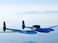 Global Flyer flying high with misty mountains in distance.